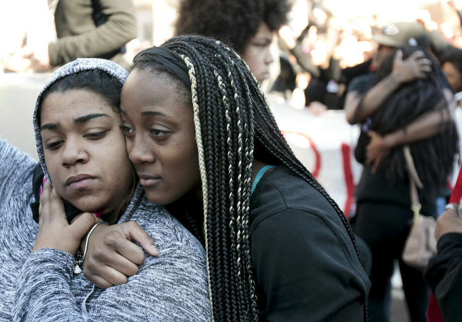 Mariah Stevens of Madison, Wis., left, is hugged by Destiny Marshall of Atlanta during a protest of the shooting of Tony Robinson at the state Capitol Monday, March 9, 2015, in Madison, Wis. Robinson, 19, was fatally shot Friday night by a police officer who forced his way into an apartment after hearing a disturbance while responding to a call. Police say Robinson had attacked the officer. (AP Photo/Wisconsin State Journal, Michael P. King)