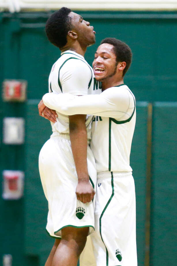 Hour photo/Chris Palermo. Zaire Wilson gets a hug from Jeremy Linton following Wilton's dunk during the Bears' Class LL state tournament first round win over Shelton High School Monday night.