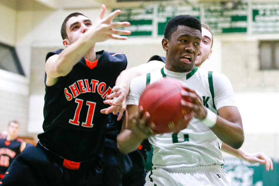 Hour photo/Chris Palermo. Zaire Wilson grabs the rebound from Shelton defenders during the Bears' Class LL state tournament first round win over Shelton High School Monday night.
