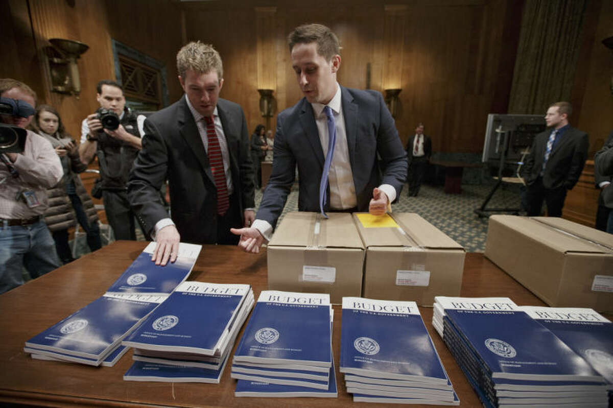 Copies of President Barack Obama?'s proposed fiscal 2015 budget are set out for distribution by Senate Budget Committee Clerk Adam Kamp, center, on Capitol Hill in Washington, Tuesday, March 4, 2014. President Barack Obama is unwrapping a nearly $4 trillion budget that gives Democrats an election-year playbook for fortifying the economy and bolstering Americans' incomes. It also underscores how pressure has faded to launch bold, new attacks on federal deficits. (AP Photo/J. Scott Applewhite)