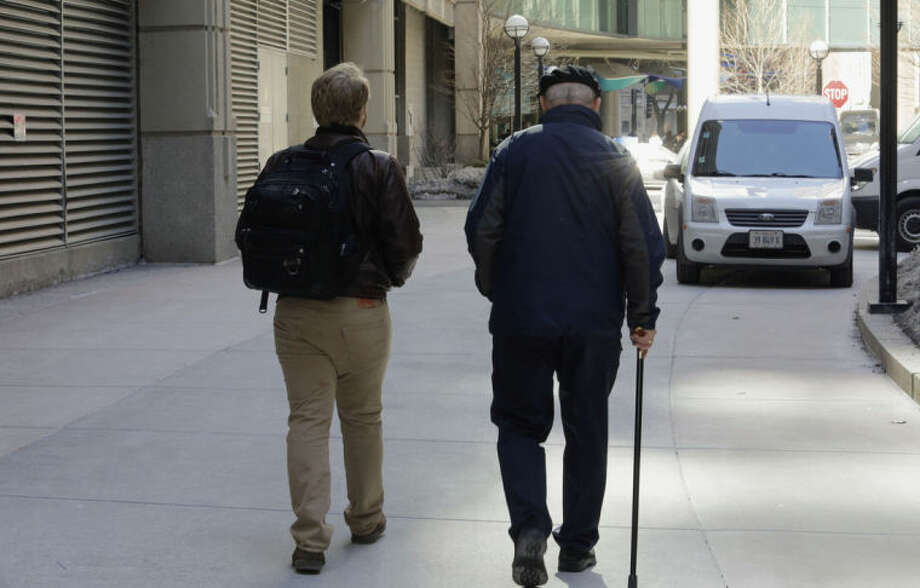"In this Feb. 28, 2014 photo, first-year Northwestern University medical student Jared Worthington, left, walks with his ""Alzheimer's buddy,"" retired physician Dan Winship in Chicago's Streeterville neighborhood. The two are part of a ""buddy"" program pairing doctors-to-be with dementia patients, pioneered at Northwestern and adopted at a handful of other medical schools. (AP Photo/Teresa Crawford)"