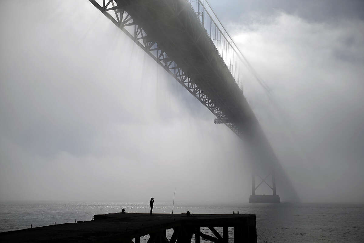 A fisherman smokes a cigarette as he waits near his rod under the April 25th bridge by the Tagus riverbank during a foggy morning, in Lisbon, Tuesday, March 10, 2015. The name of the bridge was given after the Carnations revolution that restored the democracy in Portugal in April 1974. (AP Photo/Francisco Seco)