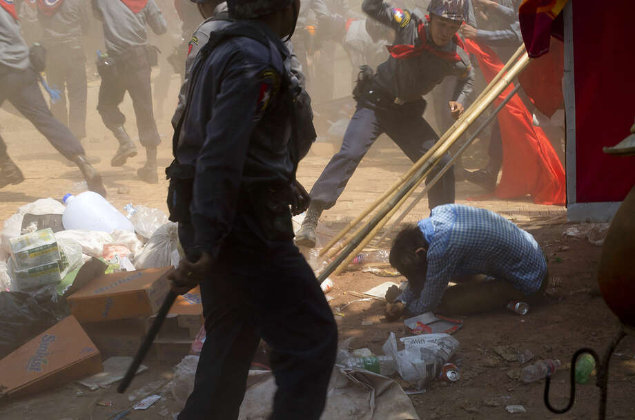 A police officer beats a student protester in Letpadan, 140 kilometers (90 miles) north of Yangon, Myanmar, Tuesday March 10, 2015. Hundreds of police were charging student protesters with batons, kicking and beating them as they dragged them into trucks, ending a days-long standoff in the Myanmar town of Letpadan. Witnesses say many of the demonstrators were injured in Tuesday's crackdown, though it was not clear how badly. (AP Photo/Gemunu Amarasinghe)