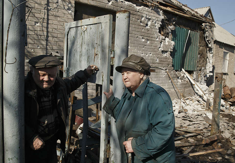 """An elderly couple stand in front of their badly damaged house in Debaltseve, Ukraine, Monday, March 9, 2015. More than 6,000 people have died in eastern Ukraine since the start of the conflict almost a year ago that has led to a """"merciless devastation of civilian lives and infrastructure,"""" according to the U.N. human rights office. (AP Photo/Vadim Ghirda)"""