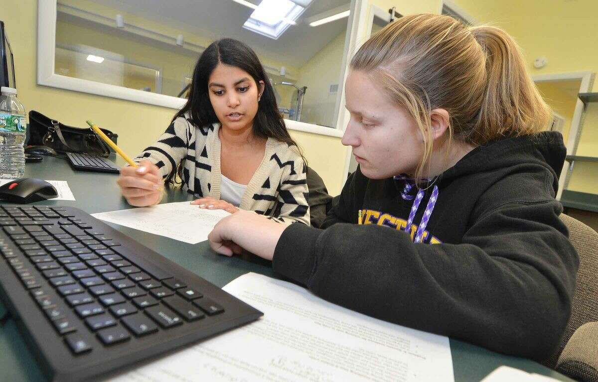 Stamford High School senior Brianna Samaranayake helps Westhill freshman Laura Carroll with her biology assignment during a recent Beyond Limits tutoring session in the Stamford Peace computer lab.