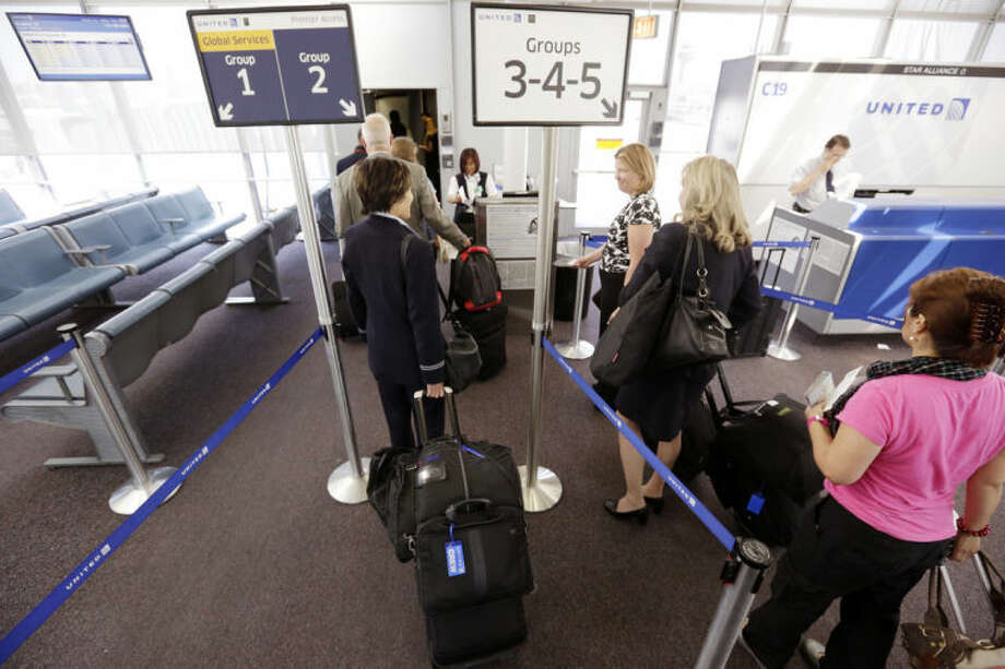 FILE - In this May 8, 2013 file photo, groups of passengers wait at a United Airlines gate to board a flight in separate numbered lanes at O'Hare International Airport in Chicago. In February 2014, United Airlines installed new bag sizers at airports and emailed its frequent fliers, reminding them of its rules (AP Photo/M. Spencer Green)