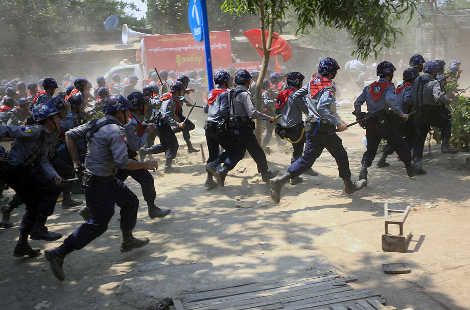 Myanmar police with batons rush towards protesters in Letpadan, 140 kilometers (90 miles) north of Yangon, Myanmar, Tuesday March 10, 2015. Hundreds of police charged student protesters with batons, ending a days-long standoff in the Myanmar town of Letpadan. Witnesses say many of the demonstrators were injured in Tuesday's crackdown, though it was not clear how badly. (AP Photo/Khin Maung Win)