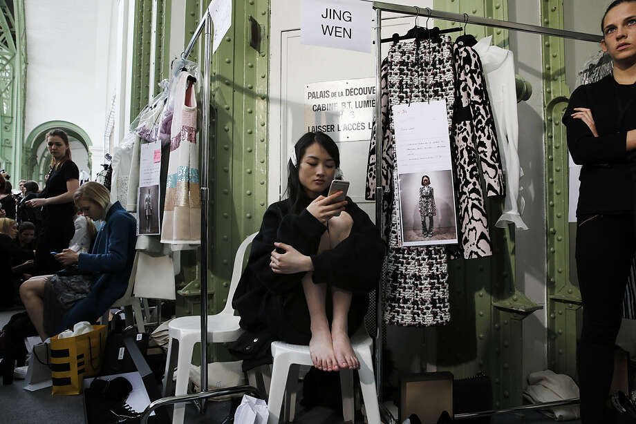 A model sits backstage as eh waits to get prepared for the Giambattista Valli's fall-winter 2015-2016 ready to wear fashion collection, presented in Paris, France, Monday, March 9, 2015. (AP Photo/Christophe Ena)