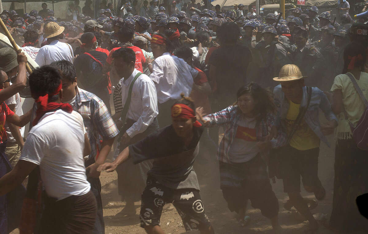 Student protesters run as police officers charge during a crackdown in Letpadan, 140 kilometers (90 miles) north of Yangon, Myanmar, Tuesday March 10, 2015. Hundreds of police were charging student protesters with batons, kicking and beating them, ending a days-long standoff in the Myanmar town of Letpadan. Witnesses say many of the demonstrators were injured in Tuesday's crackdown, though it was not clear how badly. (AP Photo/Gemunu Amarasinghe)
