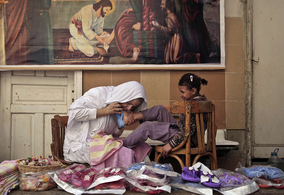 "In this Wednesday, Feb. 25, 2015 photo, Maggie Gobran, known as ""Mama Maggie"", kisses the foot of a child as she places a new slipper on her foot after washing her feet at a community development center she founded, in the Manshiet Nasr neighborhood of Cairo, Egypt. ""I want each child to know how much I love them. I appreciate them, I respect them,"" she said. Her organization, called Stephen's Children after Christianity's first martyr, has started nearly 90 such centers and she estimates they have assisted more than 30,000 low-income Egyptian families. (AP Photo/Nariman El-Mofty)"