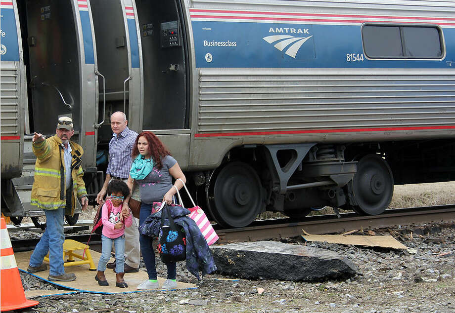 Train passenger Alyssa Coleman, right, and her little sister, Viara Hinton, are helped off of a derailed Amtrak train by workers on scene, Monday, March 9, 2015, in Halifax County, N.C. Coleman said she was traveling home to Virginia. The passenger train hit a tractor-trailer that stalled on the railroad tracks, toppling the engine onto its side and injuring several people, officials said Monday. (AP Photo/The Daily Herald, Erin Carson)