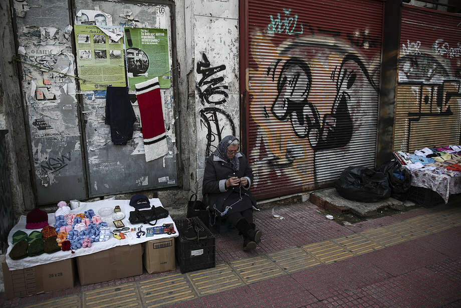 A woman knits as she sits next to her stall in Piraeus port town, west of Athens, on Tuesday, March 10, 2015. Greece is quickly running out of cash and has to repay debts this month to the International Monetary Fund — which co-funded Greece's euro240 billion bailout . (AP Photo/Yorgos Karahalis)