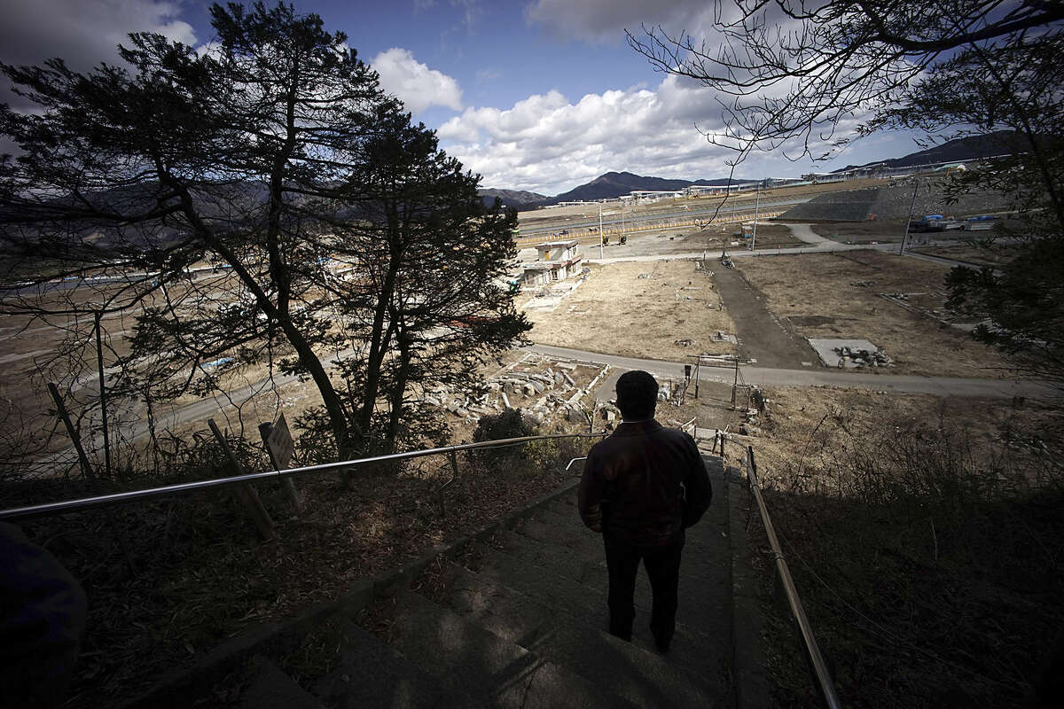 """In this Thursday, March 5, 2015 photo, Michihiro Kono, president of Yagisawa Shoten Co., looks from a hill at the site of his company's headquarters was located before the 2011 tsunami, in Rikuzentakata, Iwate Prefecture, northeastern Japan. The traditional soy-sauce maker, destroyed by the giant tsunami four years ago, has made a comeback, defying tsunami-scale odds. The secret lies in a little white bottle, named """"the miracle,"""" which holds the special ingredients that were passed down for decades. (AP Photo/Eugene Hoshiko)"""