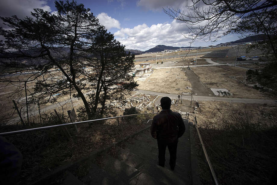 "In this Thursday, March 5, 2015 photo, Michihiro Kono, president of Yagisawa Shoten Co., looks from a hill at the site of his company's headquarters was located before the 2011 tsunami, in Rikuzentakata, Iwate Prefecture, northeastern Japan. The traditional soy-sauce maker, destroyed by the giant tsunami four years ago, has made a comeback, defying tsunami-scale odds. The secret lies in a little white bottle, named ""the miracle,"" which holds the special ingredients that were passed down for decades. (AP Photo/Eugene Hoshiko)"