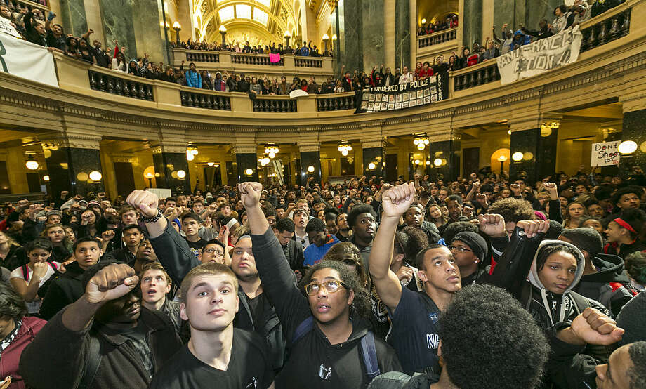 Demonstrators protest the shooting of Toly Robinson at the state Capitol Monday, March 9, 2015, in Madison, Wis. Robinson, 19, was fatally shot Friday night by a police officer who forced his way into an apartment after hearing a disturbance while responding to a call. Police say Robinson had attacked the officer. (AP Photo/Andy Manis)