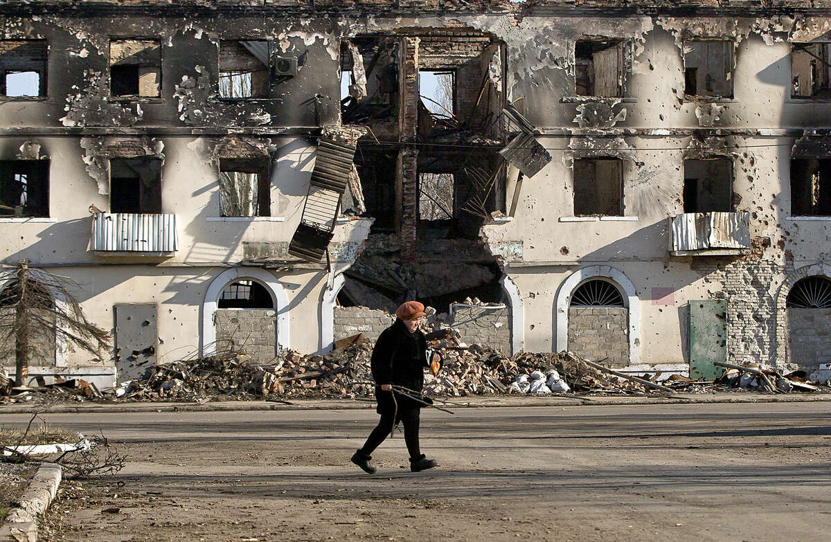 """An elderly woman walks by a destroyed building in Vuhlehirsk, Ukraine, Monday, March 9, 2015. More than 6,000 people have died in eastern Ukraine since the start of the conflict almost a year ago that has led to a """"merciless devastation of civilian lives and infrastructure,"""" according to the U.N. human rights office. (AP Photo/Vadim Ghirda)"""