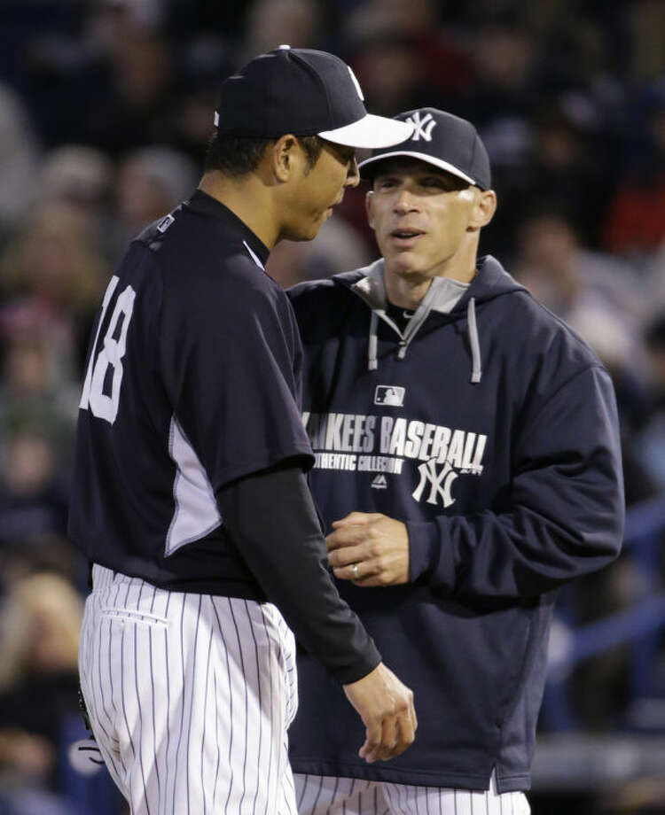 New York Yankees manager Joe Girardi, right, congratulates starting pitcher Hiroki Kuroda after taking the ball from him in the third inning of a spring training baseball game against the Detroit Tigers in Tampa, Fla., Friday, March 7, 2014. (AP Photo/Kathy Willens)