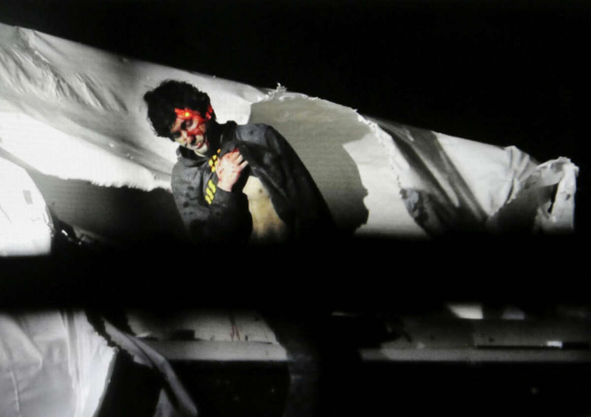 FILE - In this April 19, 2013 file photo provided by the Massachusetts State Police, Boston Marathon bombing suspect Dzhokhar Tsarnaev, bloody and disheveled with the red dot of a sniper's rifle laser sight on his head, emerges from a boat at the time of his capture by law enforcement authorities in Watertown, Mass. The prosecution presented as evidence Tuesday, March 10, 2015, during Tsarnaev's federal death penalty trial, photos of the handwritten note found inside the boat where he was captured four days after the bombings. (AP Photo/Massachusetts State Police, Sean Murphy, File)