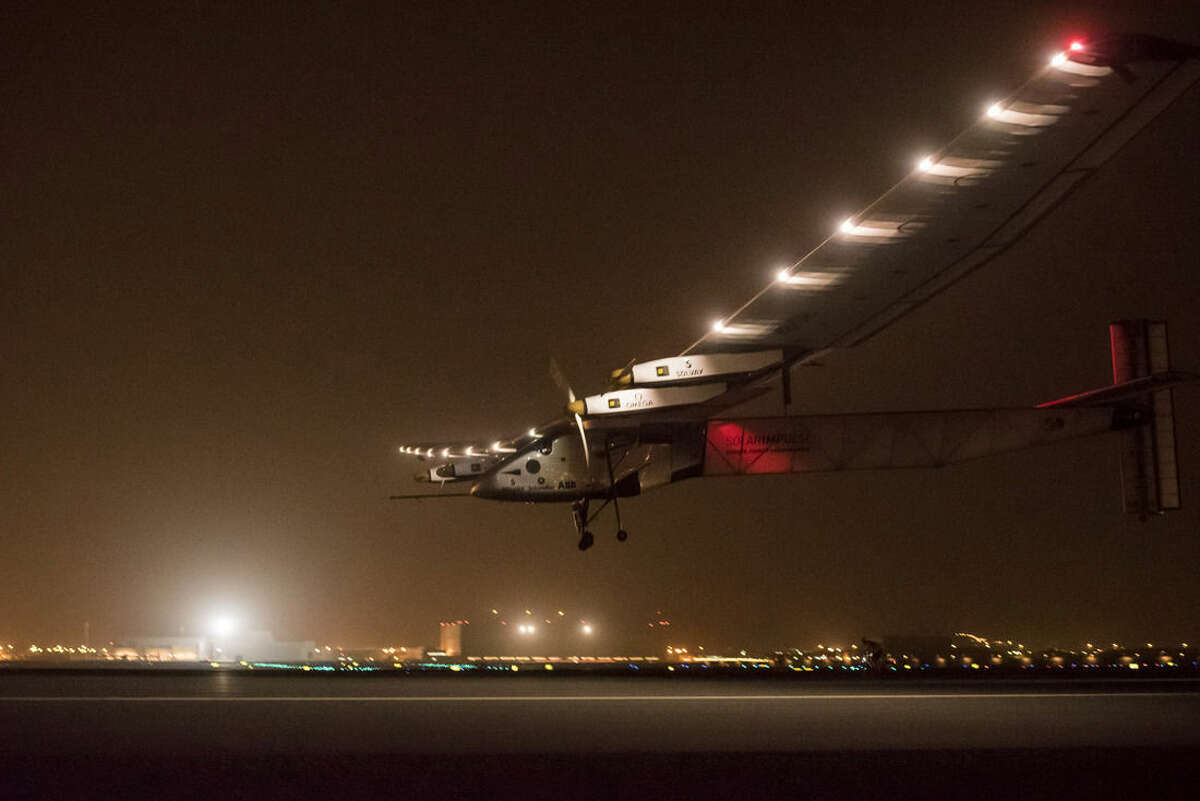 In this Monday, March 9, 2015 photo released by Solar Impulse, a Swiss solar-powered plane lands in Muscat, Oman, after it took off from Abu Dhabi early Monday, marking the start of the first attempt to fly around the world without a drop of fuel. Solar Impulse founder Andre Borschberg was at the controls of the single-seater when it took off from the Al Bateen Executive Airport. (AP Photo/Jean Revillard and Olga Stefatou, Solar Impulse)