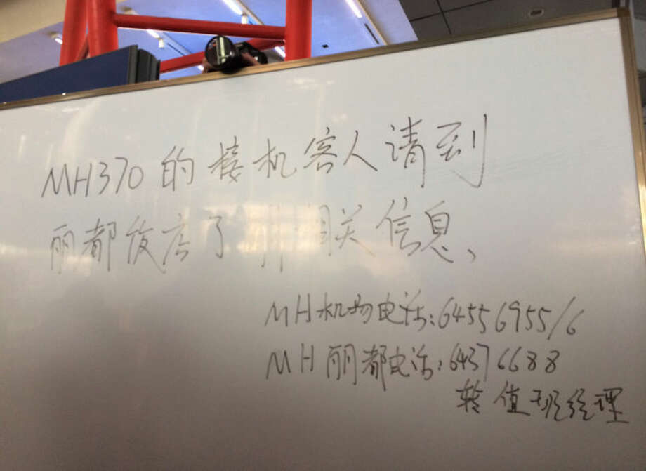 This photo released by China's Xinhua News Agency, shows an notification for family members of passengers aboard flight MH370 of Malaysia Airlines that the plane is delayed, at Beijing Capital International Airport in Beijing, China on March 8, 2014. A Malaysia Airlines Boeing 777-200 carrying 239 people lost contact with air traffic control early Saturday morning on a flight from Kuala Lumpur to Beijing, and international aviation authorities still hadn't located the jetliner several hours later. (AP Photo/Xinhua, Luo Xiaoguang) NO SALES