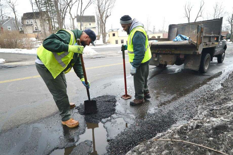 Hour Photo/Alex von Kleydorff Crews from Norwalk Public Works were out on Tuesday repairing potholes. On East Ave. a crew uses the last of the 2000 lb's of cold patch before going back for more.