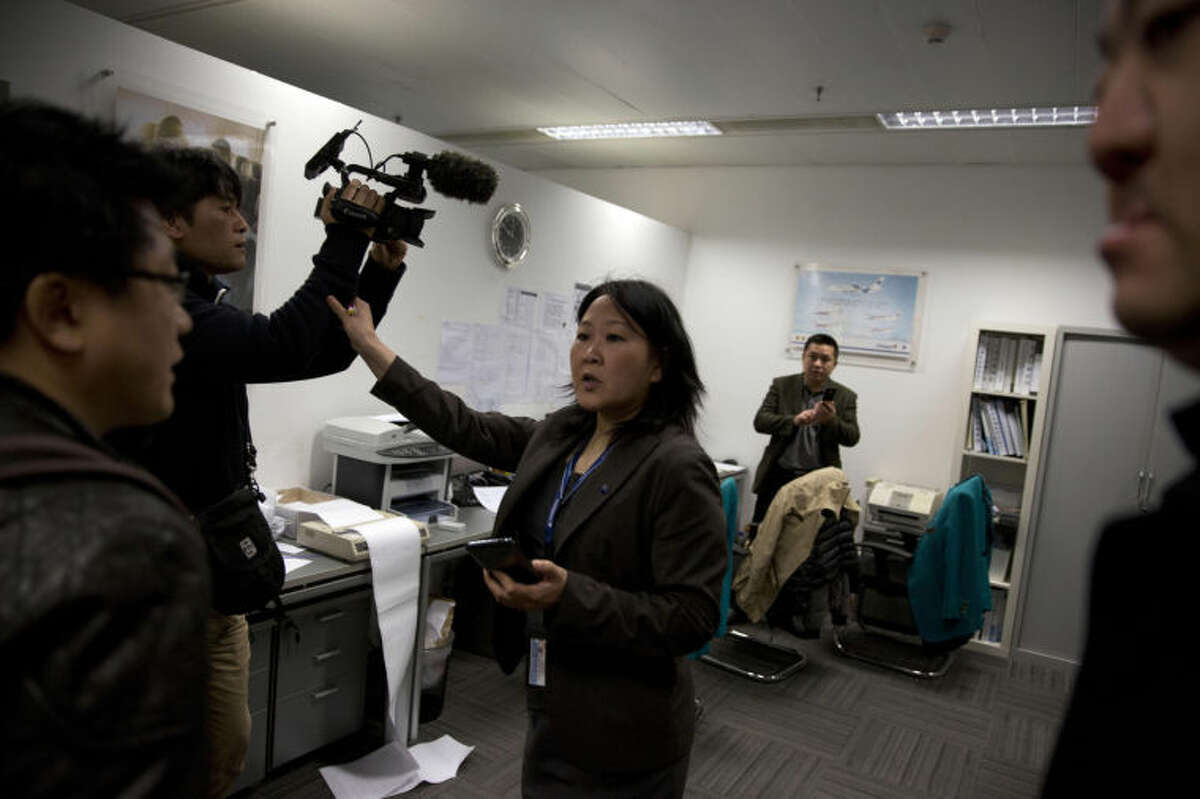 A staff member at the Malaysian Airlines' office in Beijing's International Airport reacts to journalists in Beijing, China, Saturday, March 8, 2014. A Malaysia Airlines Boeing 777-200 carrying 239 people lost contact with air traffic control early Saturday morning on a flight from Kuala Lumpur to Beijing, and international aviation authorities still hadn't located the jetliner several hours later. (AP Photo/Ng Han Guan)