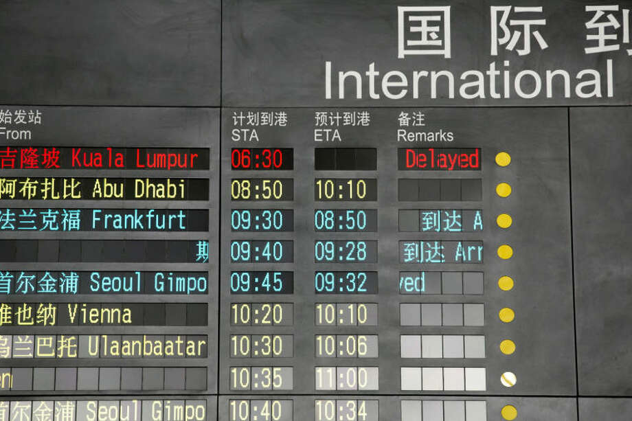 The arrival board at the International Airport in Beijing, China shows a Malaysian airliner is delayed, Saturday, March 8, 2014. A Malaysia Airlines Boeing 777-200 carrying 239 people lost contact with air traffic control early Saturday morning on a flight from Kuala Lumpur to Beijing, and international aviation authorities still hadn't located the jetliner several hours later. (AP Photo/Ng Han Guan)