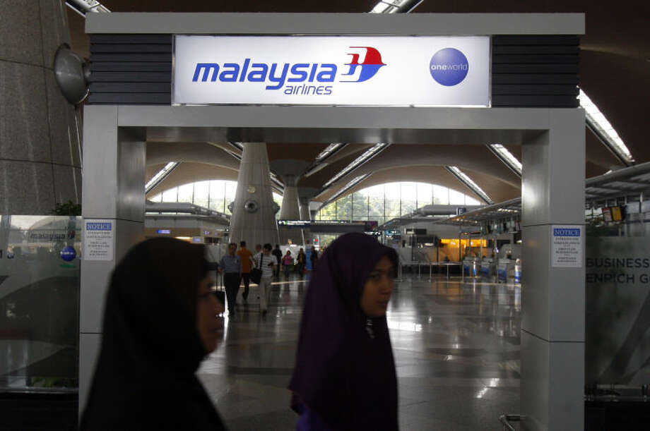 Passengers walk past a signboard of Malaysia Airlines at Kuala Lumpur International Airport in Sepang, outside Kuala Lumpur, Malaysia, Saturday, March 8, 2014. A Malaysia Airlines Boeing 777-200 carrying 239 people lost contact with air traffic control early Saturday morning on a flight from Kuala Lumpur to Beijing, and international aviation authorities still hadn't located the jetliner several hours later. (AP Photo/Lai Seng Sin)