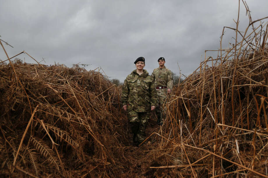 British army officers walk on a WW1 practise trench as they pose for the photographers in Gosport, southern England, Thursday, March 6, 2014. This overgrown and oddly corrugated patch of heathland on England's south coast was once a practice battlefield, complete with trenches, weapons and barbed wire. Thousands of troops trained here to take on the Germany army. After the 1918 victory _ which cost 1 million Britons their lives _ the site was forgotten, until it was recently rediscovered by a local official with an interest in military history. Now the trenches are being used to reveal how the Great War transformed Britain _ physically as well as socially. As living memories of the conflict fade, historians hope these physical traces can help preserve the story of the war for future generations. (AP Photo/Lefteris Pitarakis)