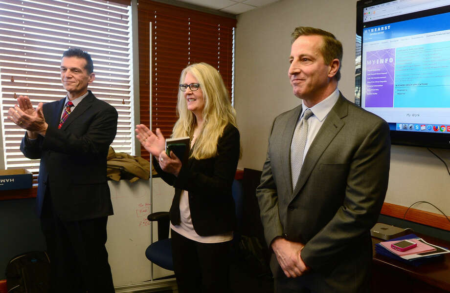Senior V.P. of Sales and Marketing Rich Medeiros, Executive Editor Barbara T. Roessner and Group Publisher Paul Barbetta celebrate the announcement that Hearst Connecticut Media Group has acquired the Norwalk Hour and Wilton Villager newspapers.