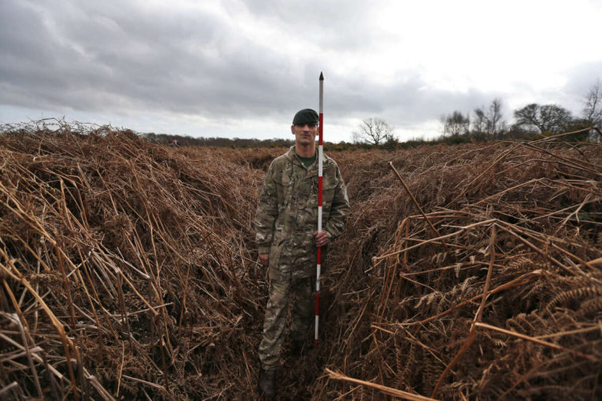 British army Rifleman Stuart Gray, holding a pole to measure the height, walks on a WW1 practise trench as he poses for the photographers in Gosport, southern England, Thursday, March 6, 2014. This overgrown and oddly corrugated patch of heathland on England?'s south coast was once a practice battlefield, complete with trenches, weapons and barbed wire. Thousands of troops trained here to take on the Germany army. After the 1918 victory _ which cost 1 million Britons their lives _ the site was forgotten, until it was recently rediscovered by a local official with an interest in military history. Now the trenches are being used to reveal how the Great War transformed Britain _ physically as well as socially. As living memories of the conflict fade, historians hope these physical traces can help preserve the story of the war for future generations. (AP Photo/Lefteris Pitarakis)