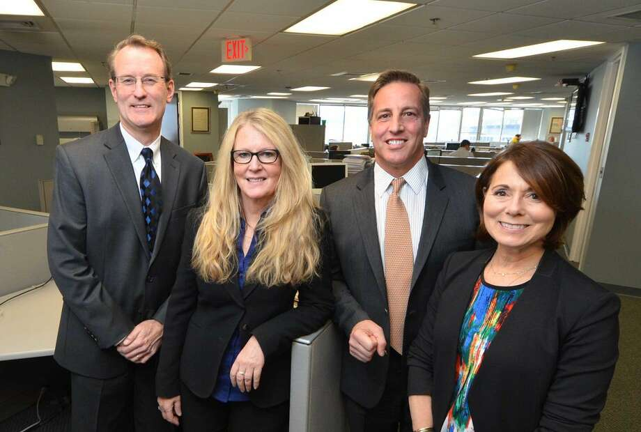 Associate Publisher Mark Lukas, Executive Editor Barbara T. Roessner, Group Publisher Paul Barbetta and Executive Producer Sheryl Shaker celebrate the announcement that Hearst Connecticut Media Group has acquired the Norwalk Hour and Wilton Villager newspapers.