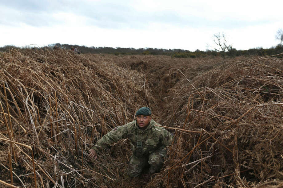 British army Lance Corporal Rob Walters kneels on a WW1 practise trench as he poses for the photographers in Gosport, southern England, Thursday, March 6, 2014. This overgrown and oddly corrugated patch of heathland on England's south coast was once a practice battlefield, complete with trenches, weapons and barbed wire. Thousands of troops trained here to take on the Germany army. After the 1918 victory _ which cost 1 million Britons their lives _ the site was forgotten, until it was recently rediscovered by a local official with an interest in military history. Now the trenches are being used to reveal how the Great War transformed Britain _ physically as well as socially. As living memories of the conflict fade, historians hope these physical traces can help preserve the story of the war for future generations. (AP Photo/Lefteris Pitarakis)