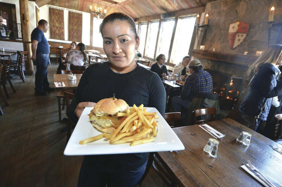 Hour photo / Alex von KleydorffServer Marina Bonilla heads to the dining room with a Cajun Stout Burger with smoked bacon and tabasco at The Little Pub on Danbury Road. This is just one of the many Restaurant Week options for this coming week.