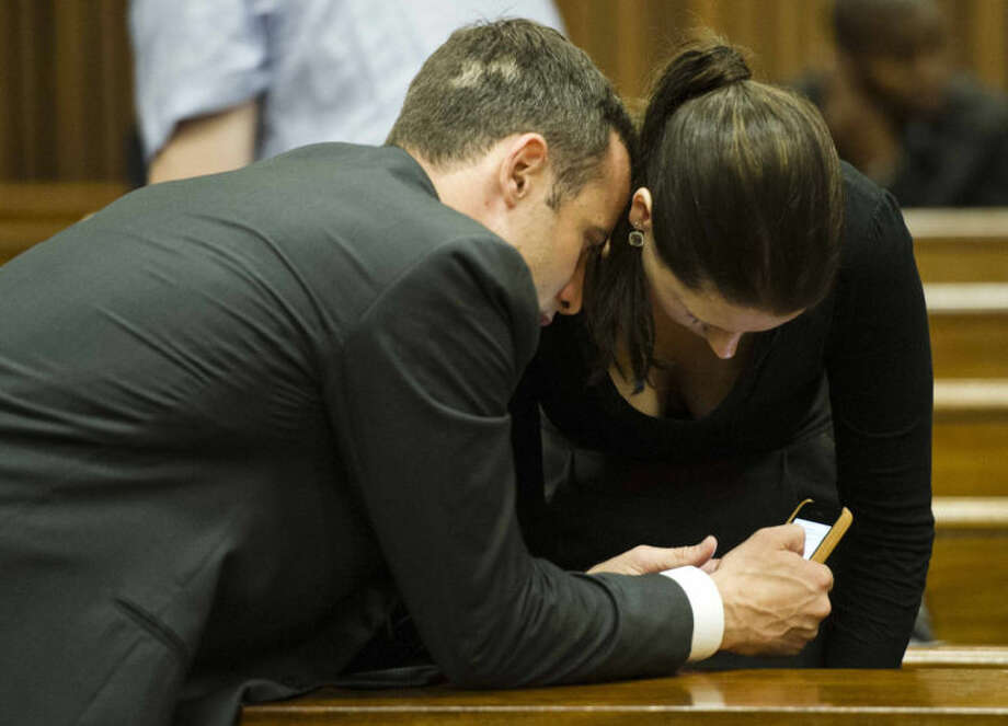 Oscar Pistorius, left, shows his mobile phone to sister Aimee on the fifth day of his trial at the high court in Pretoria, South Africa, Friday, March 7, 2014. Pistorius is charged with murder for the shooting death of his girlfriend, Reeva Steenkamp, on Valentines Day in 2013. (AP Photo/Theana Breugem, Pool)