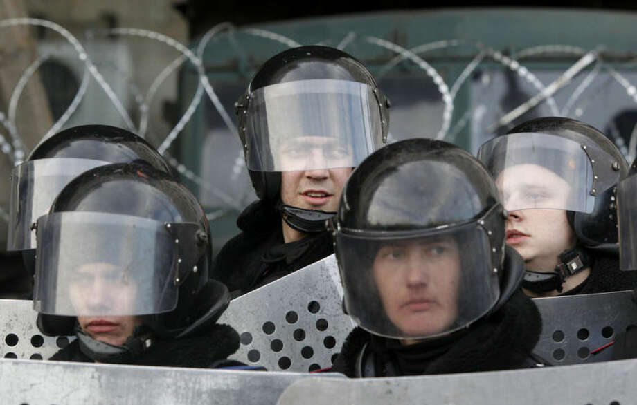 Ukrainian riot police stand at the entrance of the regional administrative building during a pro Russian rally in Donetsk, Ukraine, Saturday, March 8, 2014. Pro Russian activists continued to gather on Saturday in the eastern Ukrainian city of Donetsk, as Russia was reported to be reinforcing its military presence in Crimea. (AP Photo/Sergei Grits)
