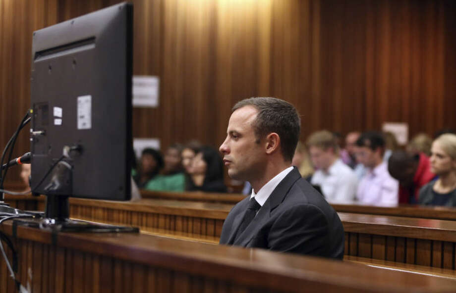 Oscar Pistorius, foreground, sits in the dock during his trial at the high court in Pretoria, South Africa, Friday, March 7, 2014. Pistorius is charged with murder for the shooting death of his girlfriend, Steenkamp, on Valentines Day in 2013. (AP Photo/Themba Hadebe, Pool)