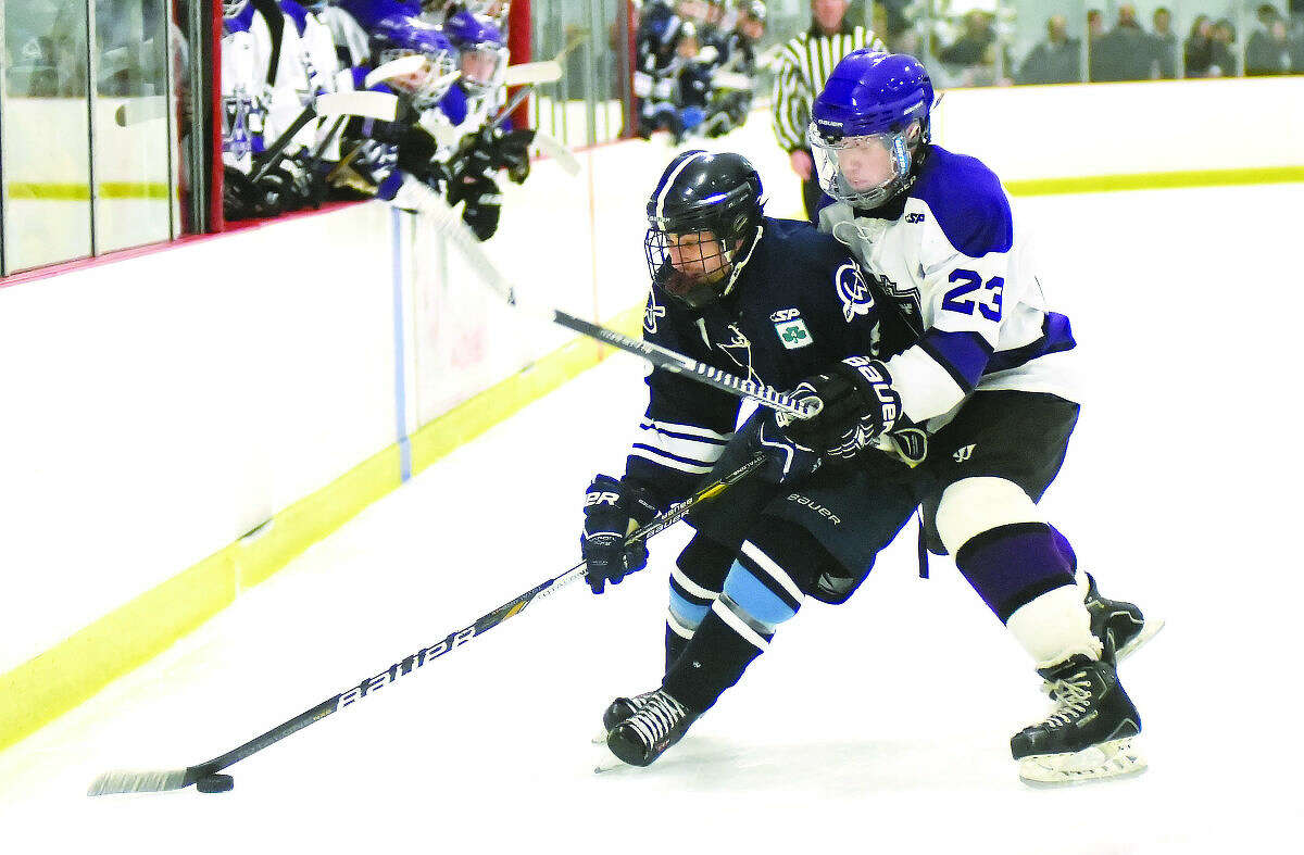 Wilton's Luke Rizzo, left, gathers the puck as he is checked from behind by North Branford's Tanner Opie during Tuesday's CIAC Division 2 state tournament game at the Northford Ice Pavilion. (Hour photo/John Nash)