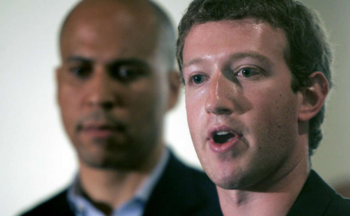 FILE - In this Sept. 25, 2010 file photo, Mark Zuckerberg, right, founder and CEO of Facebook talks about his donation of $100 million to help Newark public schools during a news conference in Newark, N.J. With Zuckerberg is Newark mayor Cory Booker and N.J. Gov. Chris Christie, not in picture. More than three years after Zuckerberg committed $100 million toward remaking Newark?'s struggling schools, the district is engulfed in a dispute over proposed large-scale teacher layoffs that is threatening to derail wider reform efforts. (AP Photo/Rich Schultz)
