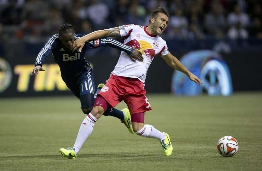 New York Red Bulls' Armando, right, of Spain, reacts as he tackles Vancouver Whitecaps' Darren Mattocks, of Jamaica, during first half MLS soccer action in Vancouver, B.C., on Saturday March 8, 2014. (AP Photo/The Canadian Press, Darryl Dyck)