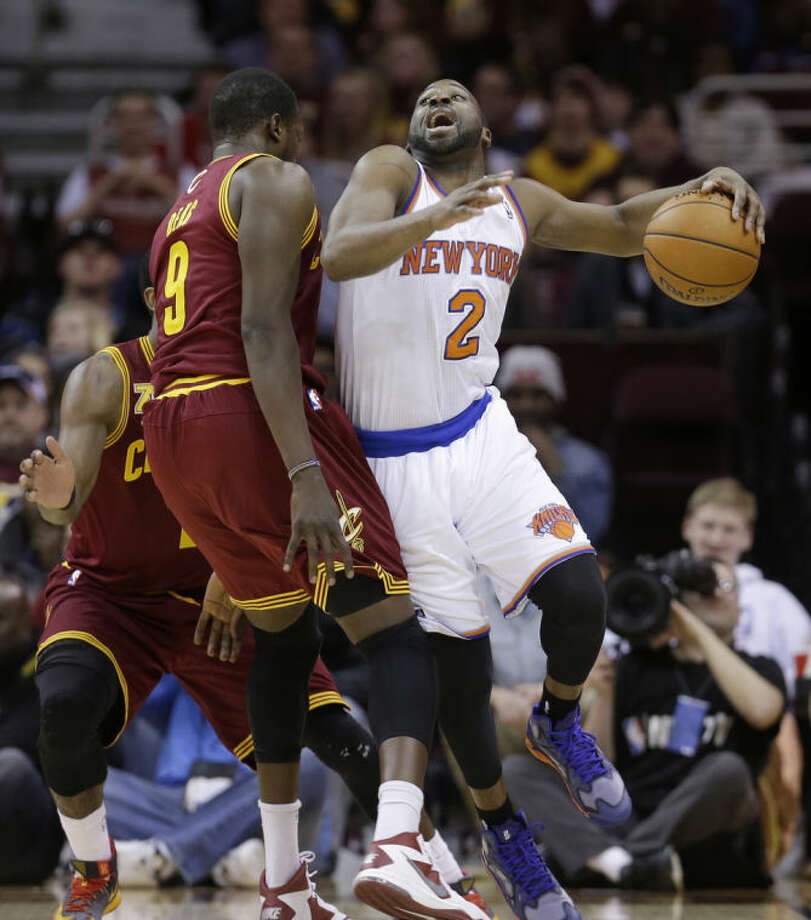New York Knicks' Raymond Felton (2) drives past Cleveland Cavaliers' Luol Deng, (9) during the first quarter of an NBA basketball game Saturday, March 8, 2014, in Cleveland. (AP Photo/Tony Dejak)