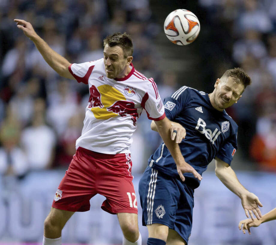 New York Red Bulls' Eric Alexander, left, and Vancouver Whitecaps' Jordan Harvey vie for the ball during first half MLS soccer action in Vancouver, B.C., on Saturday March 8, 2014. (AP Photo/The Canadian Press, Darryl Dyck)