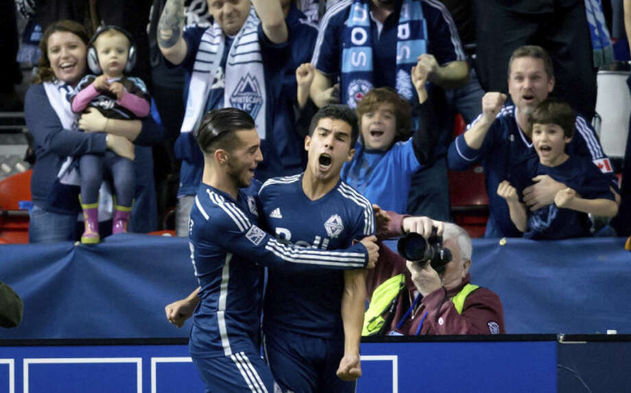 Vancouver Whitecaps' Russell Teibert, left, and Sebastian Fernandez, of Uruguay, celebrate Fernandez's goal against the New York Red Bulls during second half MLS soccer action in Vancouver, B.C., on Saturday March 8, 2014. (AP Photo/The Canadian Press, Darryl Dyck)