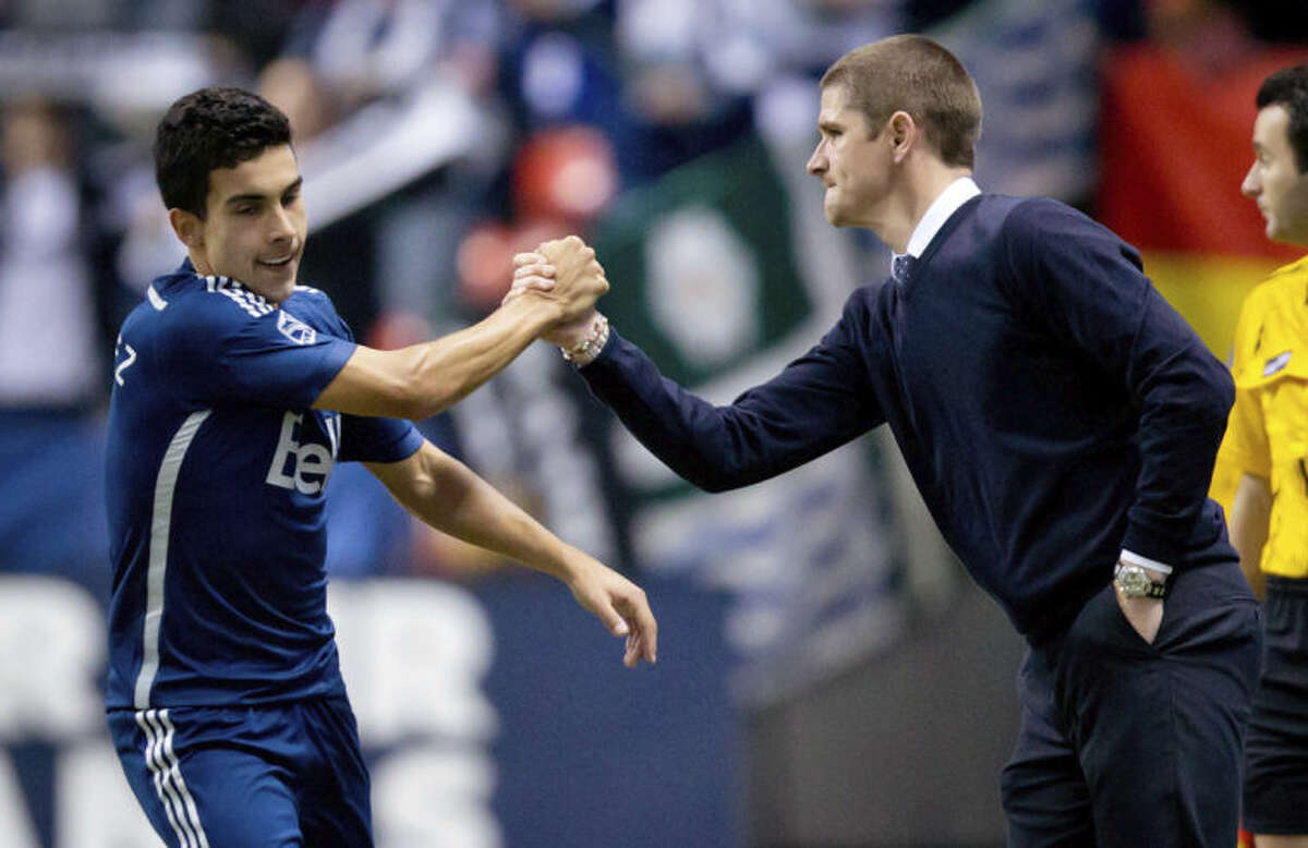 Vancouver Whitecaps' Sebastian Fernandez, left, of Uruguay, and head coach Carl Robinson celebrate Hernandez's goal against the New York Red Bulls during second half MLS soccer actionin Vancouver, B.C., on Saturday, March 8, 2014. (AP Photo/The Canadian Press, Darryl Dyck)