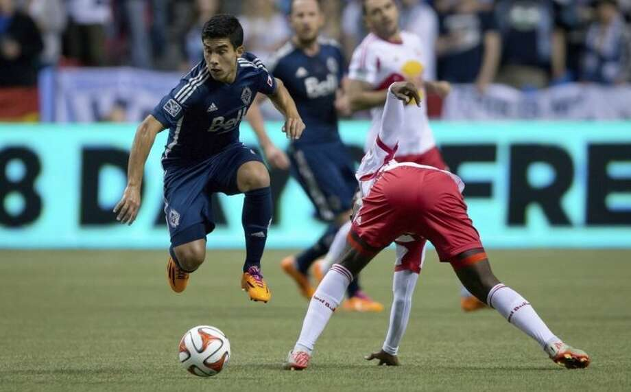 Vancouver Whitecaps' Sebastian Fernandez, left, of Uruguay, avoids the tackle from New York Red Bulls' Peguy Luyindula, of France, during first half MLS soccer game action in Vancouver, B.C., on Saturday March 8, 2014. (AP Photo/The Canadian Press, Darryl Dyck)