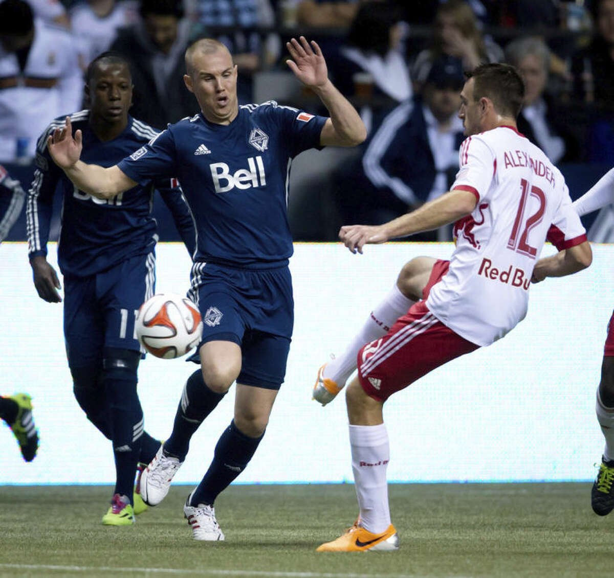 Vancouver Whitecaps' Kenny Miller, left, of Scotland, defends against New York Red Bulls' Eric Alexander during first half MLS soccer action in Vancouver, B.C., on Saturday, March 8, 2014. (AP Photo/The Canadian Press, Darryl Dyck)