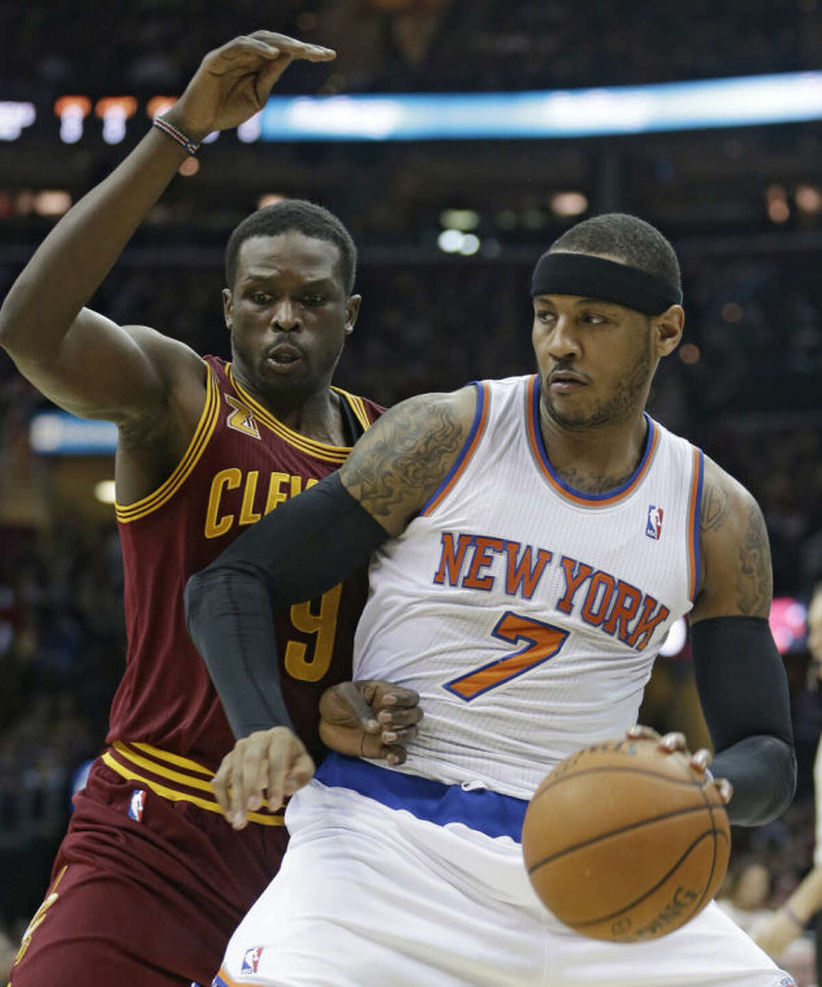New York Knicks' Carmelo Anthony (7) drives past Cleveland Cavaliers' Luol Deng, (9) during the first quarter of an NBA basketball game Saturday, March 8, 2014, in Cleveland. (AP Photo/Tony Dejak)