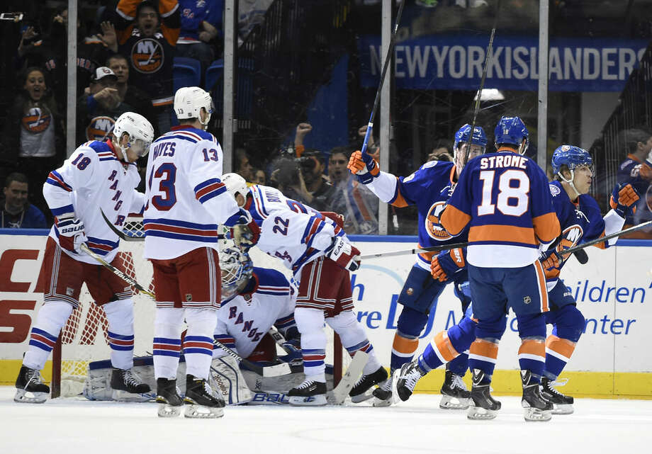 New York Islanders' Anders Lee (27), Ryan Strome (18) and center Brock Nelson (29) celebrate Lee's goal as New York Rangers' Dan Boyle (22), Kevin Hayes (13) and Marc Staal (18) gather in front of goalie Cam Talbot (33) during the first period of an NHL hockey game on Tuesday, March 10, 2015, in Uniondale, N.Y. (AP Photo/Kathy Kmonicek)