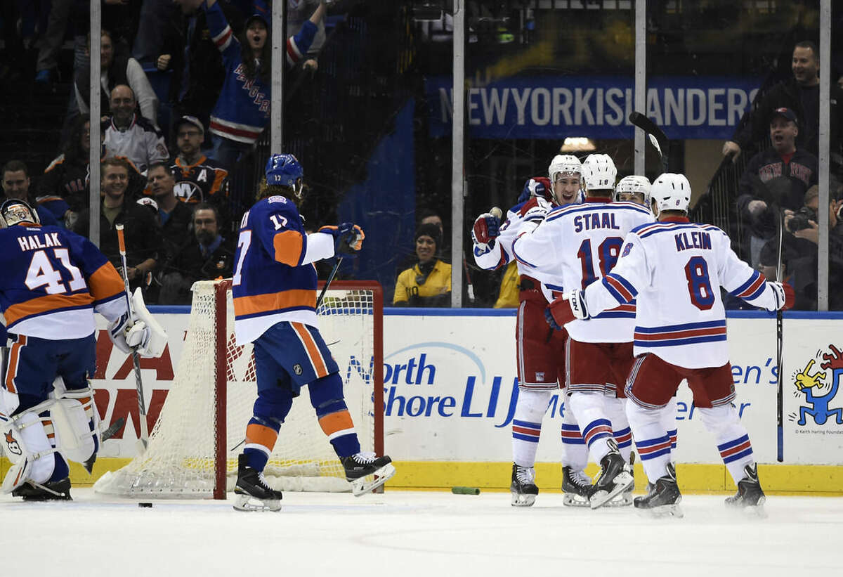 New York Rangers right wing Kevin Hayes, back, defenseman Marc Staal (18) and defenseman Kevin Klein (8) celebrate Hayes's goal as New York Islanders left wing Matt Martin (17) and goalie Jaroslav Halak (41) look on in the second period of an NHL hockey game Tuesday, March 10, 2015, in Uniondale, N.Y. (AP Photo/Kathy Kmonicek)