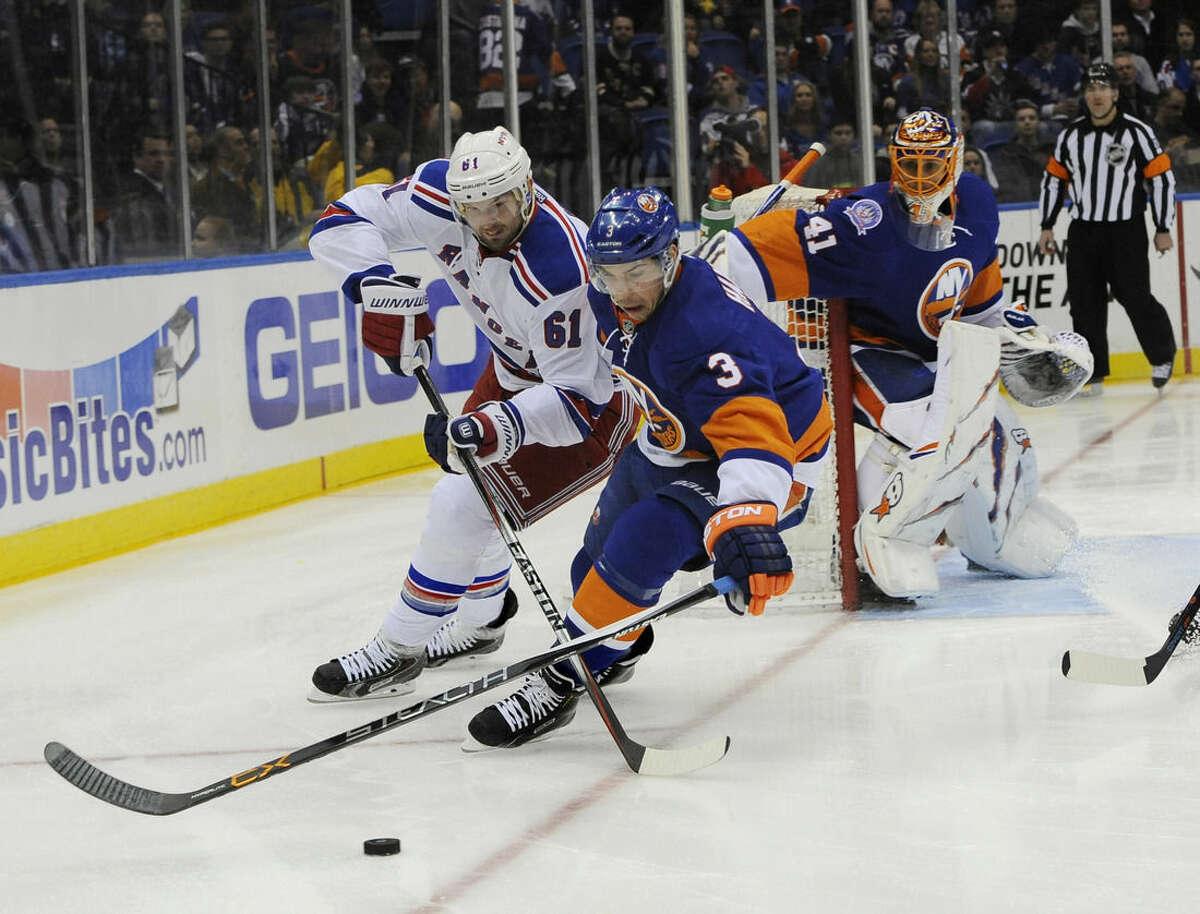 New York Rangers left wing Rick Nash (61) and New York Islanders defenseman Travis Hamonic (3) battle for the puck as New York Islanders goalie Jaroslav Halak (41) defends in the first period of an NHL hockey game Tuesday, March 10, 2015, in Uniondale, N.Y. (AP Photo/Kathy Kmonicek)